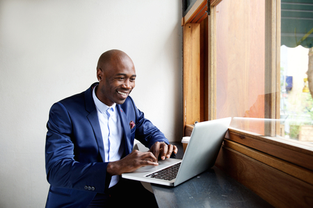 Retrato de hombre de negocios africano feliz que se sienta en un café y trabajar en la computadora portátil Foto de archivo