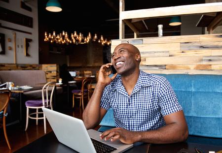 Portret van lachende man praten over de mobiele telefoon tijdens de vergadering in een cafe met een laptop