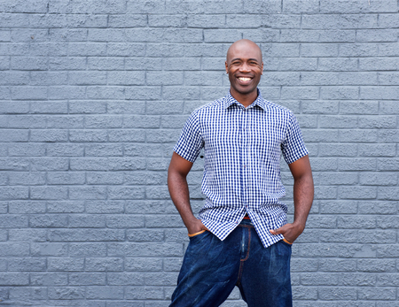 casual fashion: Portrait of confident african man smiling against gray background