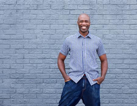 modelos hombres: Retrato del hombre africano conf�a sonriente sobre un fondo gris