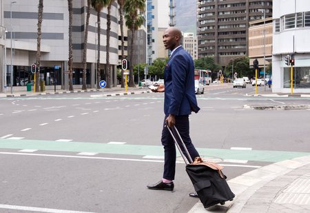 black business men: Full length portrait of a business man walking with pull bag in the city Stock Photo