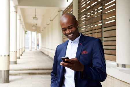 Portret van gelukkige oudere Afrikaanse zakenman met een mobiele telefoon