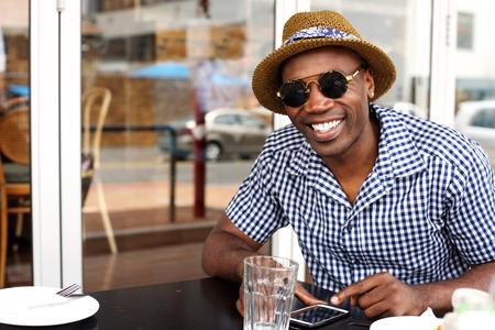 携帯電話でカフェに座って満足しているアフリカ系アメリカ人の肖像画間近します。