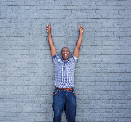Portrait of cheerful man standing with his hands raised against a gray wall Stock Photo