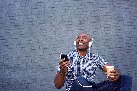 mannequin africain: Portrait d'un homme afro-américain souriant écoutant de la musique sur un casque