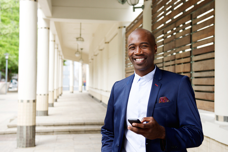 old cell phone: Portrait of confident african businessman with a mobile phone standing outdoors Stock Photo