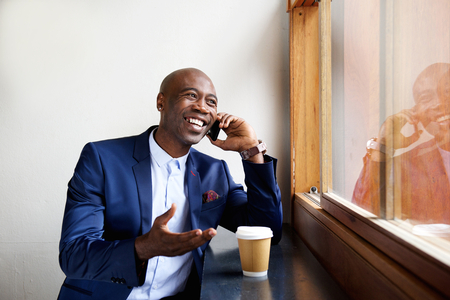 cool guy: Portrait of happy businessman sitting in a cafe talking on cell phone Stock Photo