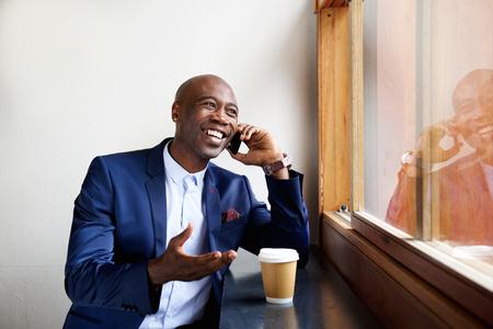hombres negros: Retrato de hombre de negocios feliz que se sienta en un café hablando por teléfono celular