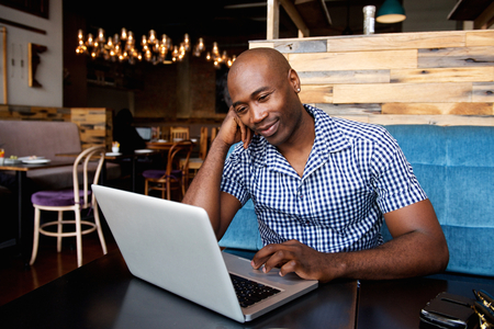 hombres negros: Retrato del hombre africano relajado sentado en una mesa de café usando la computadora portátil