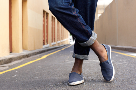 denim jeans: Close up low angle man crossed legs and shoes