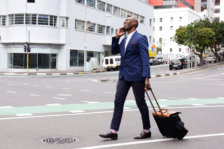 Full length portrait of a successful businessman traveling with his suitcase and talking on cell phone