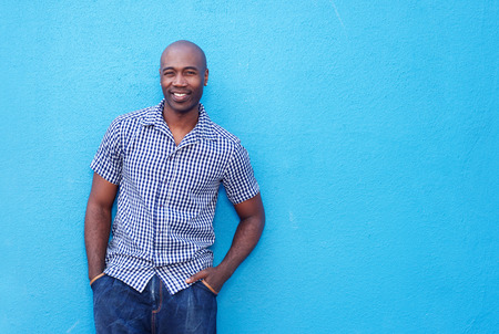 cool guy: Portrait of an attractive cool african guy standing against a blue wall Stock Photo