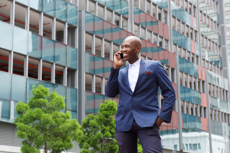 black guy: Portrait of african businessman talking on mobile phone in the city street Stock Photo
