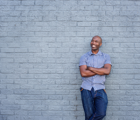 an adult person: Portrait of smiling african man standing with his arms crossed against gray background Stock Photo
