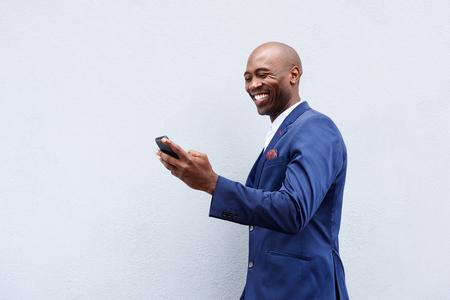 Portret van een glimlachende zakenman kijken naar mobiel Stockfoto