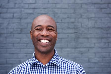 회색 벽에 서있는 웃는 흑인 남자의 초상화를 닫습니다