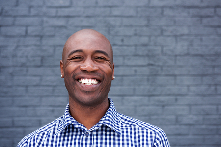 old man standing: Close up portrait of smiling african man standing against a gray wall