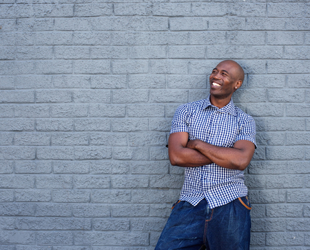 african america: Portrait of smiling african america man looking away with his arms crossed