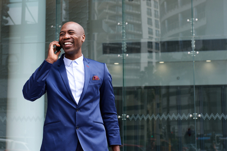 Portrait of african business executive walking and talking on cell phone Reklamní fotografie