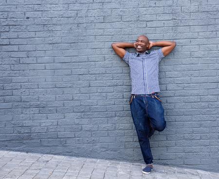 hombres negros: retrato de cuerpo entero del hombre sonriente de pie con las manos detrás de la cabeza contra un backround gris