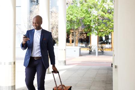 Portrait der Geschäftsmann mit einer Tasche und Handy unterwegs