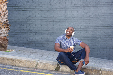 enjoy space: Portrait of happy man sitting by a street and listening to music and looking away