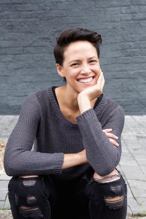 mujer alegre: Retrato de una mujer joven y moderna con la sentada del pelo corto