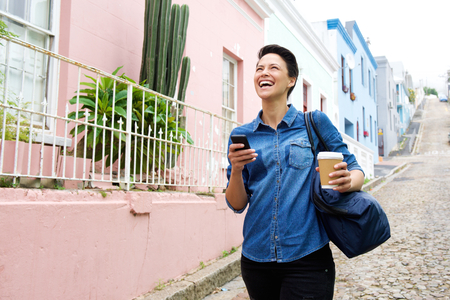 people street: Portrait of a happy young woman walking with cellphone and bag Stock Photo