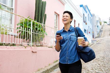 razas de personas: Retrato de una mujer joven feliz que recorre con el tel�fono celular y la bolsa