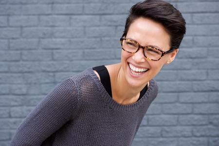 Close-up portret van een jonge vrouw lachen met een bril tegen een grijze achtergrond