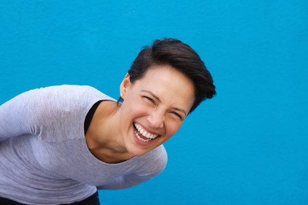 Close up portrait of a lively young woman laughing against blue background