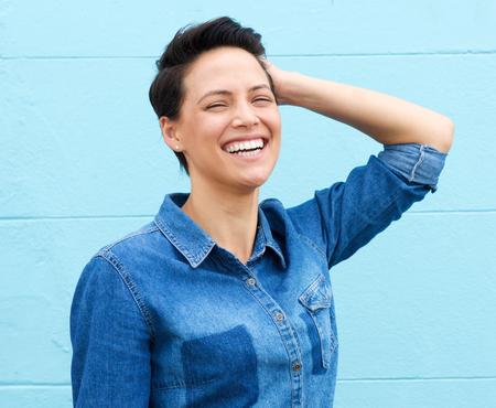 Cerca de retrato de una mujer de risa con la mano en el pelo Foto de archivo