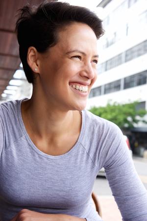 Close-up portret van een lachende jonge vrouw met kort haar lachend in de stad Stockfoto