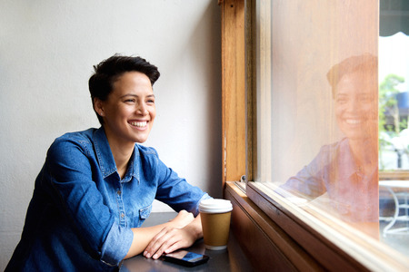 woman think: Side portrait of a smiling young woman sitting at coffee shop looking out window