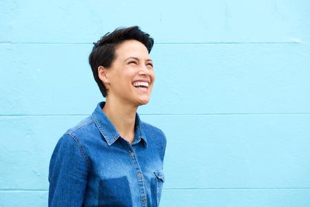 Portret van een zorgeloze jonge vrouw lachend tegen de blauwe achtergrond Stockfoto
