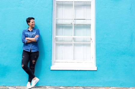 Full length portret van een gelukkige jonge vrouw staande naast venster