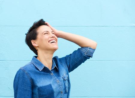 Portrait d'une jeune femme riant avec la main dans les cheveux