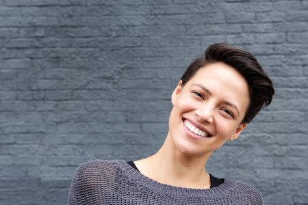 Close-up portret van een lachende jonge vrouw met kort haar tegen de grijze achtergrond Stockfoto