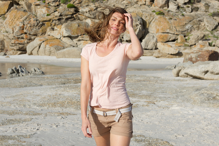 mujer alegre: Retrato de una hermosa mujer caminando en la playa con la mano en el pelo