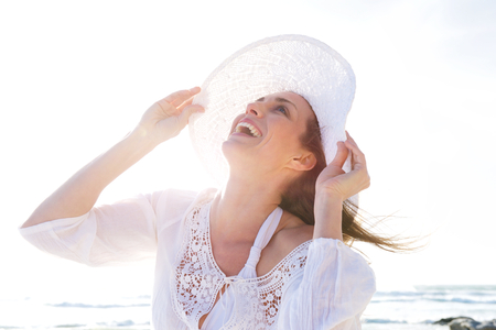 older women: Close up portrait of an older woman laughing with hat at the beach Stock Photo