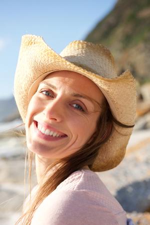 Close-up portret van een lachende vrouw met een hoed op het strand Stockfoto