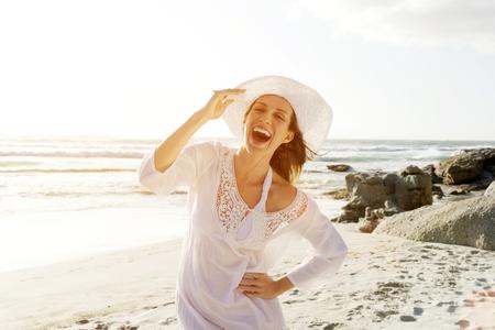 Porträt einer schönen unbeschwerte Frau zu Fuß am Strand mit Sonne Kleid und Hut