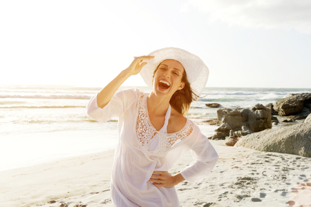 Portrait of a beautiful carefree woman walking on beach with sun dress and hat Reklamní fotografie - 51907282