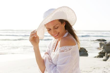 Close-up portret van een lachende oudere vrouw met een hoed op het strand Stockfoto