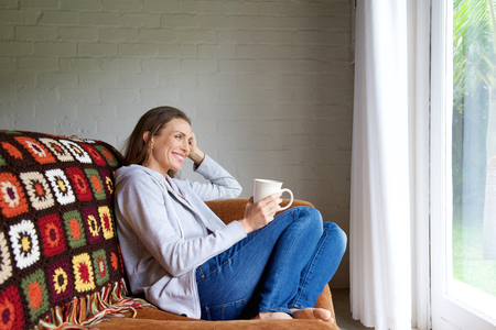 women holding cup: Portrait of a smiling older woman relaxing at home with cup of tea Stock Photo