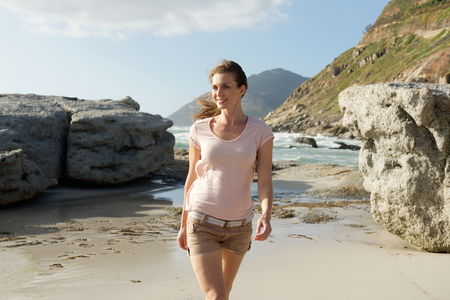 mid adults: Portrait of an attractive older female fashion model walking on beach