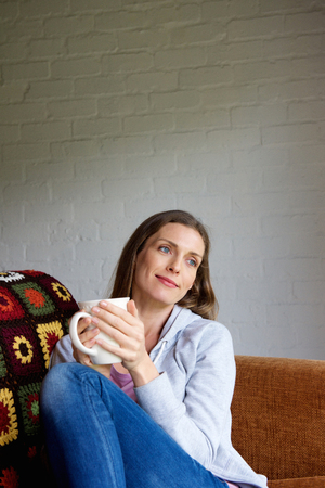women coffee: Portrait of older woman sitting at home enjoying cup of tea