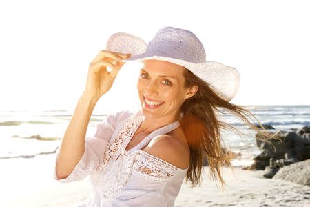 woman beach dress: Close up portrait of a beautiful woman smiling with hat at the beach