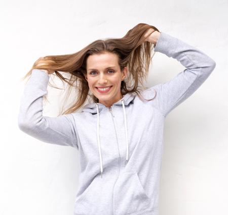 mujer sola: Retrato de una mujer mayor sonriente con la mano en el pelo Foto de archivo