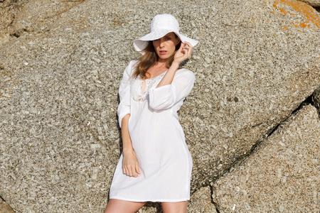mujer elegante: Retrato de un modelo de moda femenina en el vestido blanco sol y el sombrero